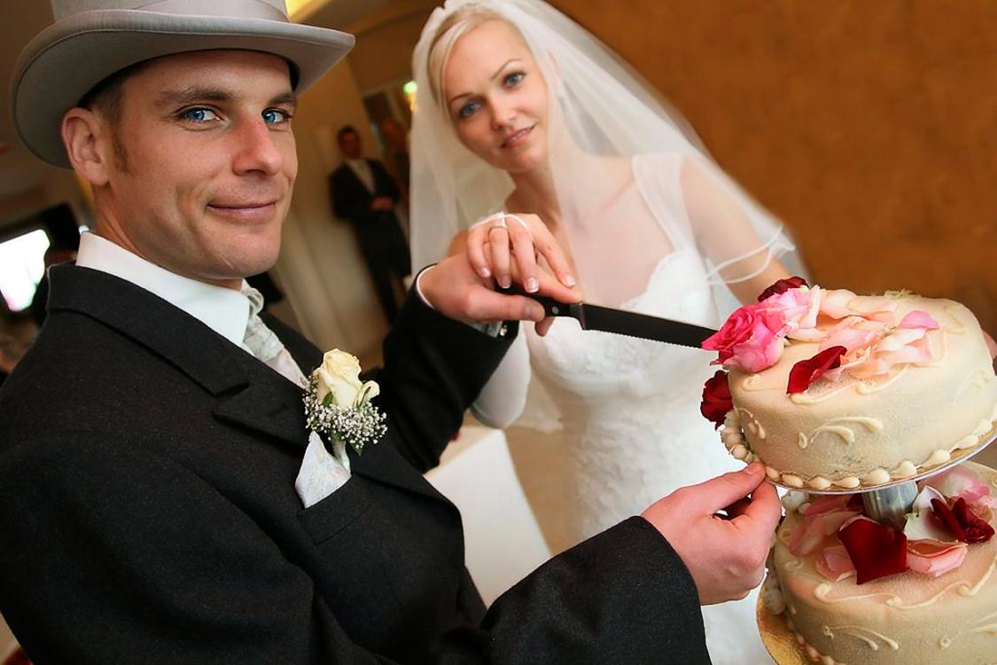 Ein Hochzeitsfoto eines Brautpaars beim Tortenanschnitt.