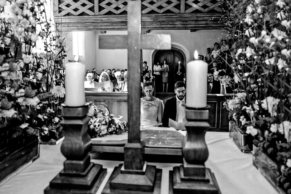 Hochzeitsfoto einer Trauung. Das Brautpaar befindet sich zwischen Kreuz und Kerze.